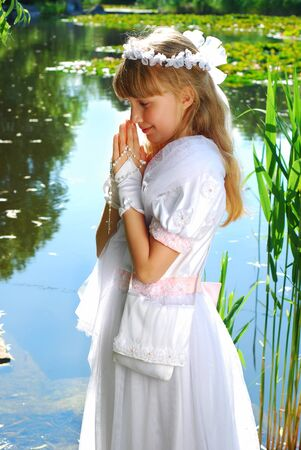 portrait of praying girl in white dress and  wreath,going to the first holy communion posing in park  Stock Photo