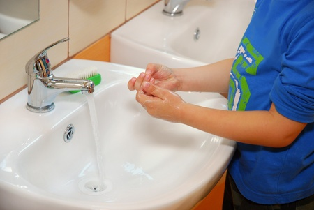 foam hand: little boy washing hands by himself in preschool`s bathroom