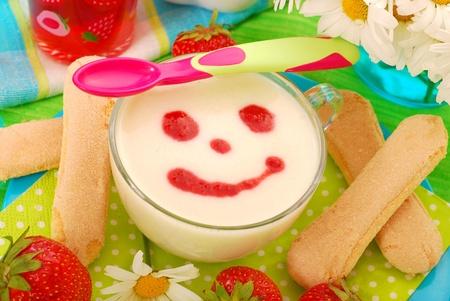 griesmeel pap met aardbeiensaus en lange vingers koekjes als dessert voor de baby Stockfoto