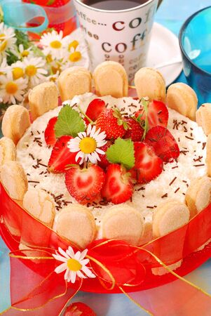 charlotte cake met aardbeien en slagroom gebonden met rood lint