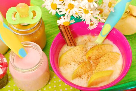 baby rice: bowl of rice pudding  dessert with apple and cinnamon ,jars with food  for baby