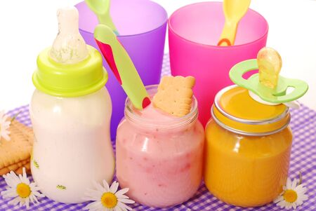 jars with  fruit yogurt , vegetable puree ,bottle of milk and biscuits as baby food isolated on white  photo
