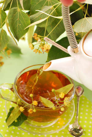 pouring hot linden tea into glass cup photo