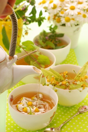 pouring hot chamomile tea into china cup photo