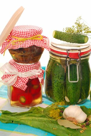 jars of homemade preserves of cherry pepper,mushrooms and pickled cucumbers isolated on white Stock Photo - 9958969