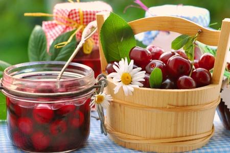 potten van zelfgemaakte cherry conserven en mand met vers fruit op de tafel in de tuin  Stockfoto