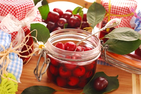 jars of homemade cherry compote and basket with fresh fruits Stock Photo - 9958996