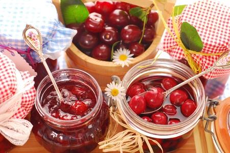 kruik van zelfgemaakte cherry conserven en mand met vers fruit