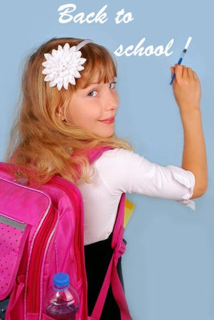 first year student: schoolgirl with pink backpack  writing BACK TO SCHOOL by brush on  blue background  Stock Photo
