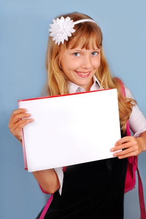 new school year: smiling schoolgirl holding blank card with empty space to write own text against blue background