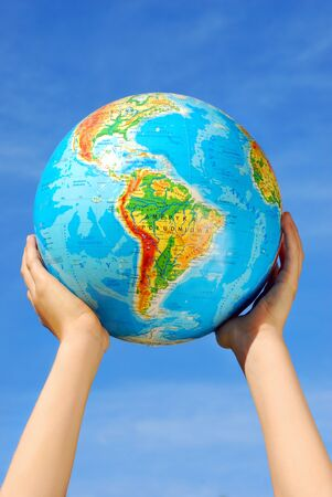 earth`s globe holding in hands against blue sky photo