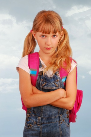 angry schoolgirl with pink backpack against cloudy  sky photo