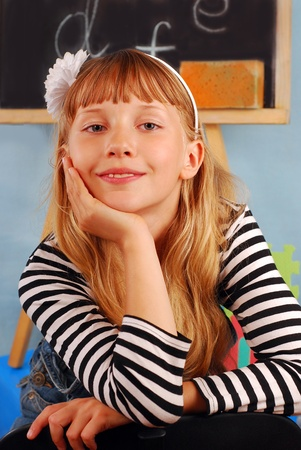 smiling schoolgirl sitting on the chair in the classroom photo