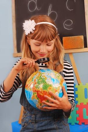 schoolgirl uniform: schoolgirl  sitting in the classroom  looking at the globe using magnifying glass