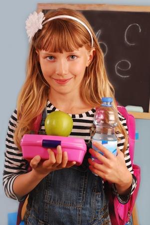 ir al colegio: colegiala en el aula con caja de almuerzo, apple y botella de agua, vamos a comer Foto de archivo