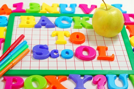 board with colorful magnetic letters that spell Back to school  photo