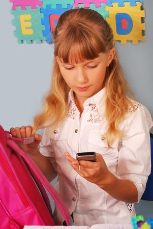 schoolgirl uniform: schoolgirl in the classroom using mobile phone