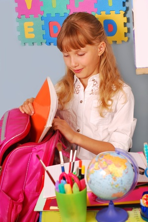 schoolgirl in the classroom packing her pink backpack photo