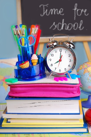 back to school supplies: school equipment and retro alarm clock on the desk in the classroom