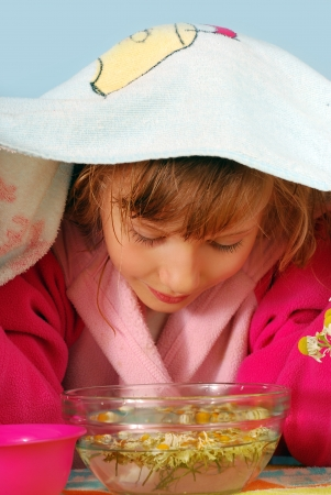 cold remedy: young girl making inhalation over a bowl with steamed camomile water Stock Photo
