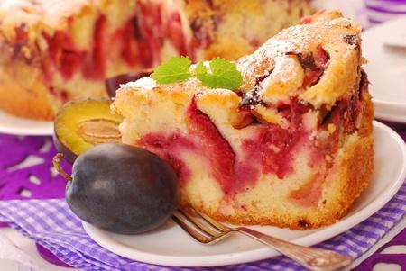a piece of homemade fresh plum cake with icing sugar