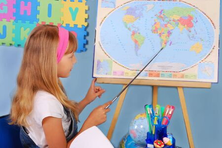 schoolgirl in the classroom on geography lesson pointing a country on the map photo