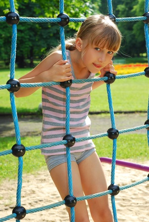 jong meisje genieten van klimtouw activiteit op de speelplaats Stockfoto