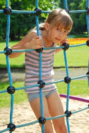 ni�os en recreo: joven disfrutando de escalada actividad de cuerda en el patio del Colegio Foto de archivo