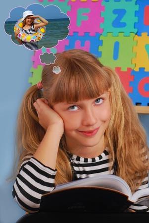 坐在教室和作梦关于假期而不是学会的微笑的女小学生