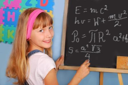 genie weinig schoolmeisje schrijven moeilijk wiskunde en fysieke formules op het bord