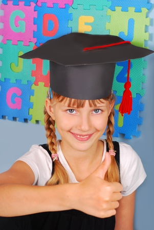happy schoolgirl in graduation cap showing good luck sign photo