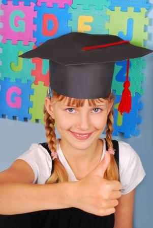 end of year: happy schoolgirl in graduation cap showing good luck sign Stock Photo