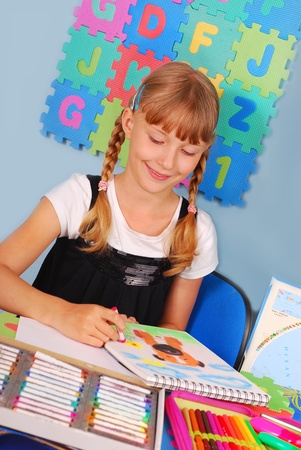 schoolgirl drawing a picture of dog with colored pencils sitting in the classroom Stock Photo - 10365246