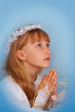 niño orando: miradas chica va a la primera comunión sobre fondo azul