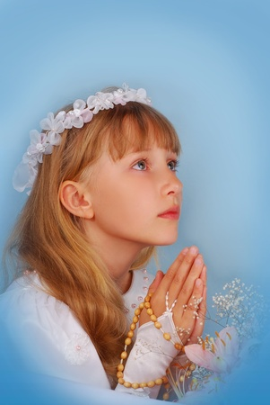 jesus hands: prying girl going to the first holy communion against blue background Stock Photo