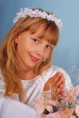 nieuwsgierige meisje naar de eerste heilige communie tegen blauwe achtergrond