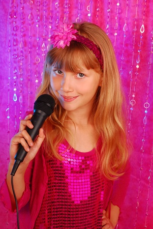 young girl in pink shiny dress singing with microphone on the stage photo