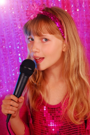 vocalist: young girl in pink shiny dress singing with microphone on the stage