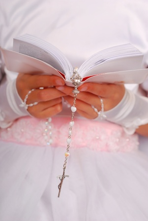 first communion: hands of prying girl going to the first holy communion