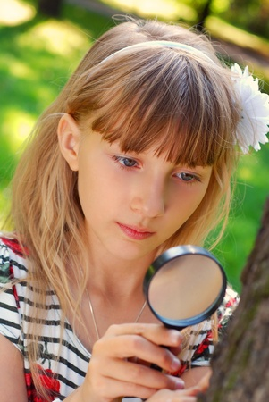 portrait of beautiful blond girl looking through magnifying glass  in the park  photo