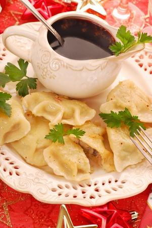 homemade  pierogi (ravioli) with mushroom and sauerkraut filling and clear red borscht (czerwony barszcz) for traditional polish christmas eve photo