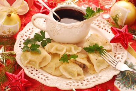 zelfgemaakte pierogi (ravioli) met champignons en zuurkool te vullen en duidelijk rode borsjt (Czerwony barszcz) voor traditionele Poolse kerstavond Stockfoto
