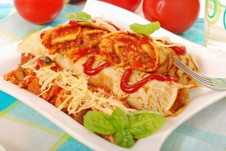 pancakes with minced meat and vegetables filling in bolognese sauce photo