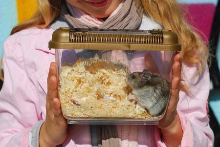 jong meisje holding hamster in draagbare transporter buiten Stockfoto