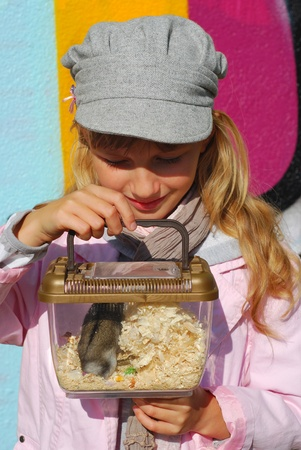 hamster: young girl holding hamster in portable transporter outdoor