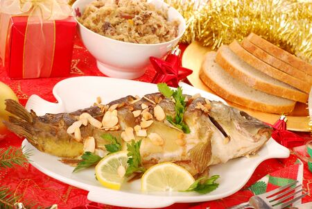 christmas dish: whole carp baked with flaked almonds served with sauerkraut (bigos) and bread on  christmas table