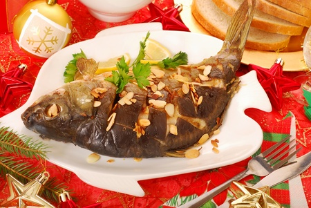 flaked: whole carp baked with flaked almonds on christmas table