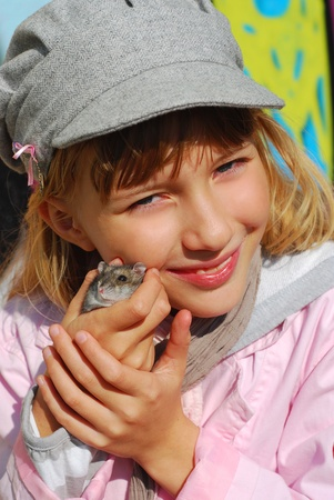 hamster: young girl holding her little hamster in hands outdoor