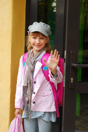 schoolmeisje met roze rugzak in te gaan op school en zwaaiend afscheid