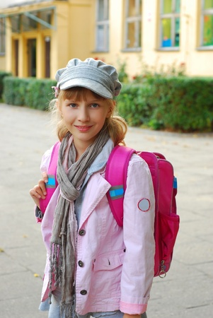 come home: schoolgirl with pink backpack going home after lessons